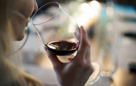 Femme faisant l'examen olfactif d'un vin rouge